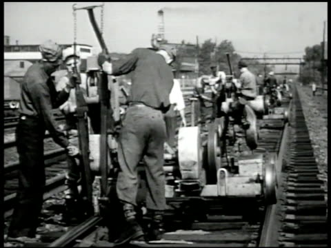 workers laying railroad tracks ms workers w/ spike pulling machine cu nails being pulled out vs crane lowering rail into place beam ms train passing... - rail transportation stock videos & royalty-free footage