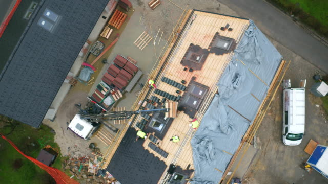 aerial workers laying tiles on the roof - construction worker stock videos & royalty-free footage