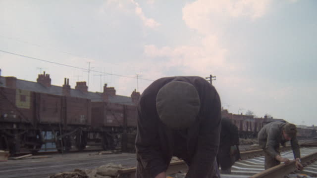 1969 montage workers laying tracks and attaching them with pandrol clips on concrete sleepers along the british railways / united kingdom - british rail stock videos & royalty-free footage