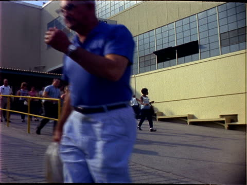 Workers leaving Lockheed factory following completion of first shift workers are African American white Hispanic young adult mid adult many carry...