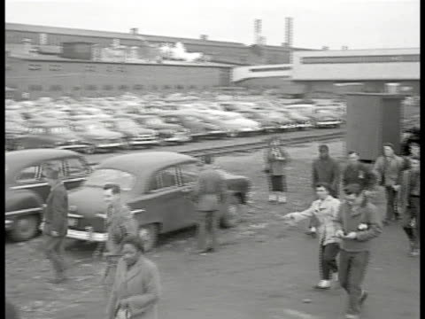 pan workers leaving plant factory parking lot bg filled w/ cars - 1953年点の映像素材/bロール