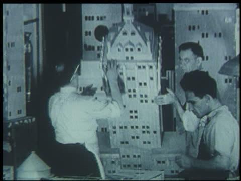 b/w 1939 workers lift building for miniature city for world's fair - getönt stock-videos und b-roll-filmmaterial
