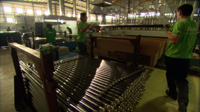 ws workers lifting long glass tubes off cart and packing them into boxes at himin solar energy group factory, dezhou, shandong, china - dreiviertelansicht stock-videos und b-roll-filmmaterial