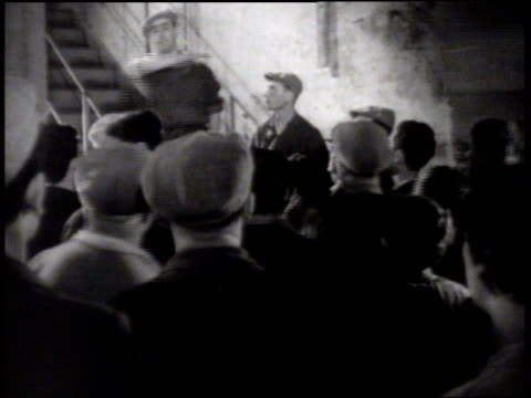 Workers listening to male standing on steps Workers talking in group Large group of people outside factory