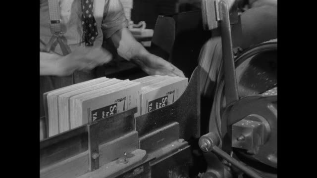 montage workers load a machine that trims the ends off of newly assembles telephone directories / london, england, united kingdom - adressbuch stock-videos und b-roll-filmmaterial