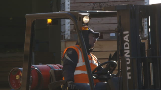 stockvideo's en b-roll-footage met workers load and unload crates at a fruit distribution centre in kent, uk. - heftruck
