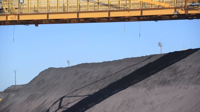 Workers look on as belts carry and stock pile iron ore at a yard of Ferroport handling company as the Acu super port prepares to load its second bulk...