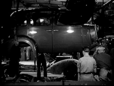 vídeos de stock e filmes b-roll de 1937 ms workers lowering car shell into place on assembly line - 1930