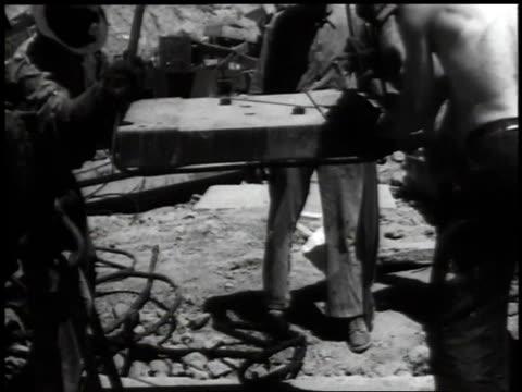 vidéos et rushes de 1941 montage workers lowering foundation concrete square onto ground with help of crane / washington d.c., united states - archéologie