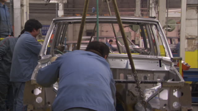 ms workers lowering steel body of jeep cherokee and disconnecting cables, beijing, china - lowering stock videos & royalty-free footage