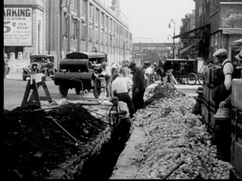 b/w 1933 montage ms pan workers lying cables in street, people in dilapidated building, newark, new jersey state, usa, audio - new jersey stock videos & royalty-free footage