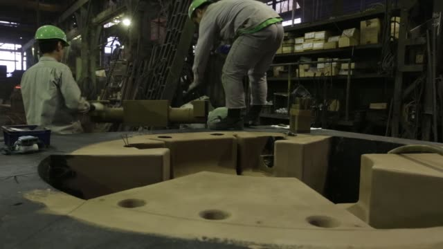 workers make a casting mold from sand at the tomiwa chuzo co foundry in kawaguchi saitama prefecture japan on tuesday march 29 2016 a worker applies... - foundry worker stock videos and b-roll footage