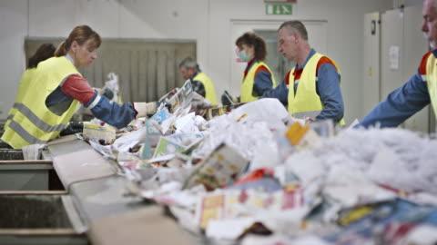 stockvideo's en b-roll-footage met ld werknemers maken laatste afval papier controleren op transportband - recycling