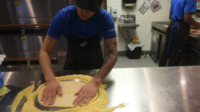 vídeos de stock, filmes e b-roll de workers making pizzas at domino's pizza theatre on 1st street in jersey city new jersey us on february 20 wide shots and close ups of a hispanic... - pie humano