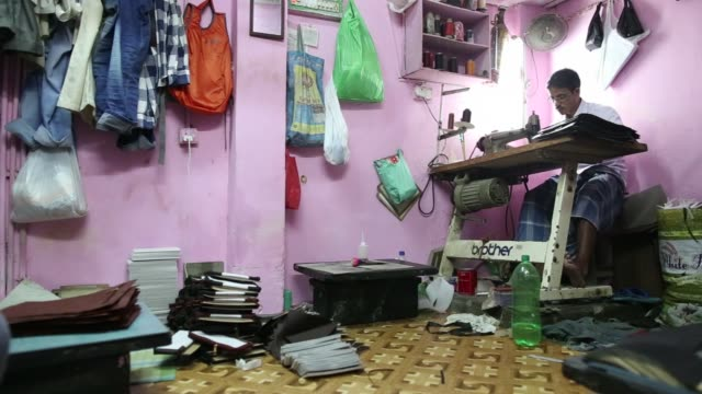 vídeos y material grabado en eventos de stock de workers manufacture wallets at a leather workshop in the dharavi area of mumbai, india, on tuesday, july 18 a worker uses a sewing machine while... - iva