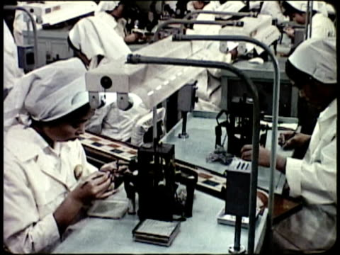 1963 MONTAGE Workers manufacturing cameras, polishing lens in assembly line / Japan