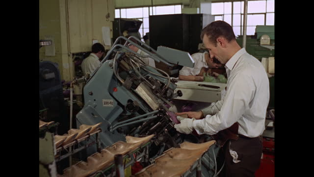 montage workers mass producing and inspecting plastic shoes in factory in united kingdom - production line stock videos & royalty-free footage