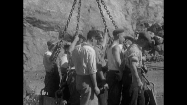 montage workers mining granite in quarry and loading in trucks / guernsey, british crown isles - 英国海峡 チャンネル諸島点の映像素材/bロール