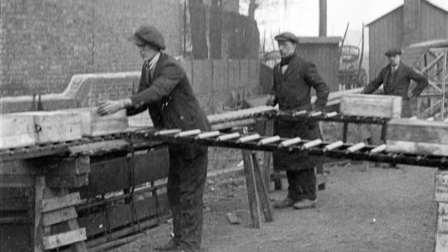 1917 ws workers moving goods onto conveyor belts / united kingdom - モノクロ点の映像素材/bロール
