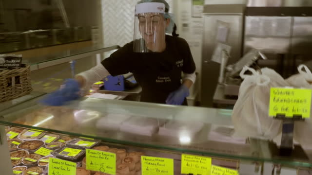 workers observing coronavirus regulations at a meat market stall - food and drink stock videos & royalty-free footage