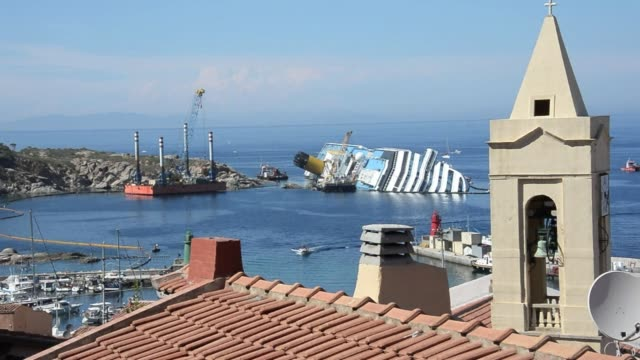 workers of the us salvage company titan and italian firm micoperi remove the swimming pool slide from the costa concordia upper deck near the harbour... - titan moon stock videos & royalty-free footage