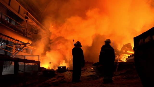 stockvideo's en b-roll-footage met workers on background smoke from smelting metal at industrial factory floor. - hoogoven