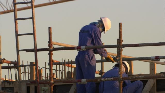MS Workers on construction site at sunrise, Dubai, United Arab Emirates