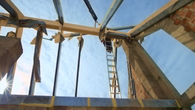 workers on the roof guiding the crane holding the wooden beam in the air - ladder stock videos & royalty-free footage