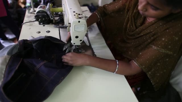 workers operate sewing machines inside a jeans factory at an apparel park in the mundargi industrial area of ballari, karnataka, india, on monday,... - jeans stock videos & royalty-free footage