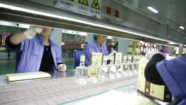 Workers pack bottles of Shuijingfang baijiu into boxes at the Yongxing distillery operated by Sichuan Swellfun Co a unit of Diageo Plc in Chengdu...