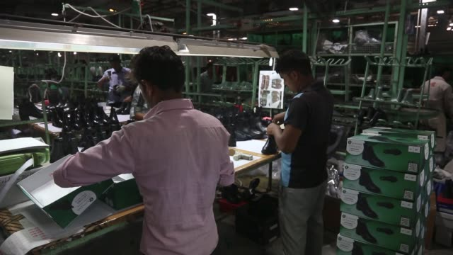 Workers package shoes into boxes after qualitycontrol inspections on the assembly line at a Virola Shoes Pvt manufacturing facility in Agra Uttar...