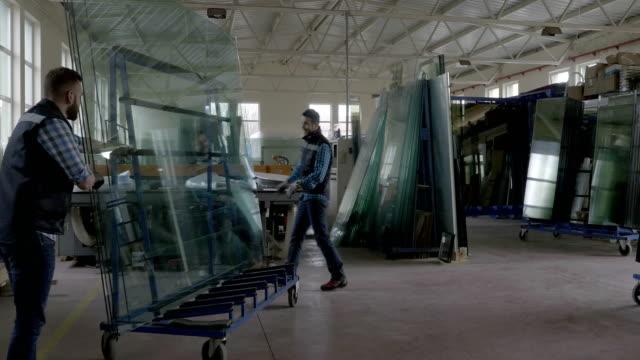stockvideo's en b-roll-footage met werknemers verpakking glazen bladen in magazijn - installeren