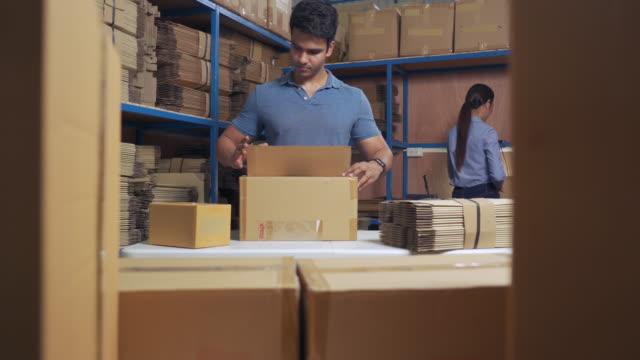 vídeos de stock, filmes e b-roll de trabalhadores embalando caixa de papelão em armazém para embarque - pacote arranjo