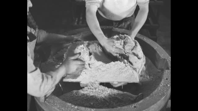 workers packing powder in circular molds / worker in foreground packing powder, worker in background pouring powder into mold from overhead dispenser... - アルミニウム点の映像素材/bロール