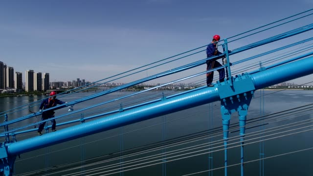 workers painting on the fengchu bridge, a three-tower suspension bridge, over hanjiang river on may 12, 2020 in xiangyang, hubei province of china. - built structure stock videos & royalty-free footage