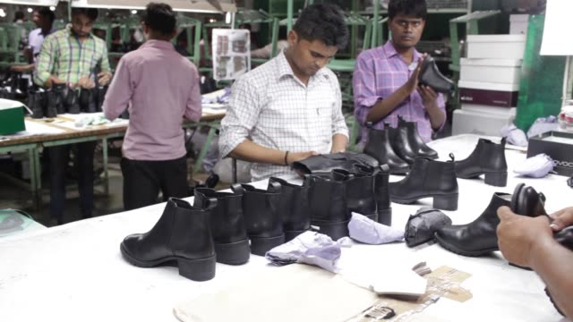 workers perform qualitycontrol inspections on shoes on the assembly line at a virola shoes pvt manufacturing facility in agra uttar pradesh india on... - shoes in a row stock videos & royalty-free footage