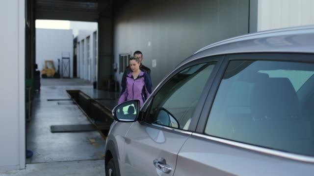 workers photographing car outside garage - laboratorio riparazioni video stock e b–roll