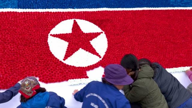 worker's place a flower's into an arrangement displaying the north korean flag ahead of the forthcoming dprkusa summit on february 25 2019 in hanoi... - g8:s toppmöte bildbanksvideor och videomaterial från bakom kulisserna