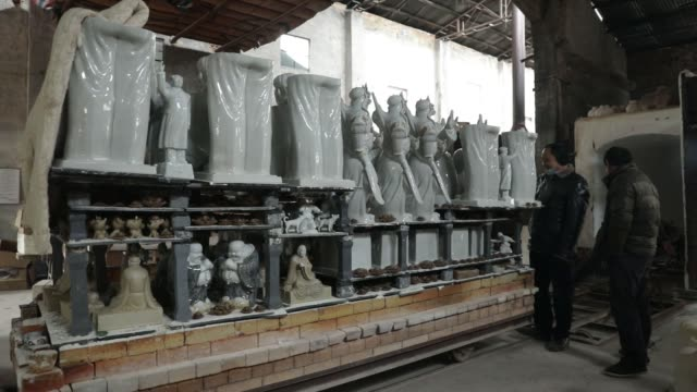 workers prepare a track for moving a cart filled with scuptures including statues of former chinese leader mao zedong from a kiln at the jingdezhen... - kiln stock videos and b-roll footage