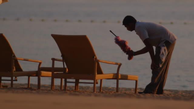 vídeos de stock, filmes e b-roll de workers prepare beach at sunrise- palm island, dubai - pano de pó