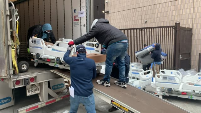 workers prepare dozens of extra medical beds as they are delivered to mount sinai hospital amid the coronavirus pandemic on march 31, 2020 in new... - new york state stock videos & royalty-free footage