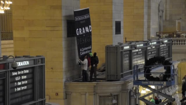 workers prepare grand central terminal grand hall for its 100 year anniversary by removing christmas ornaments and hanging up anniversary banner... - centesimo anniversario video stock e b–roll