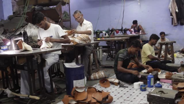 Workers prepare leather uppers for shoes in the uppers section at a Virola Shoes Pvt manufacturing facility in Agra Uttar Pradesh India on Thursday...