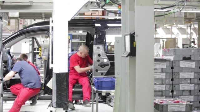 workers prepare the body shell of a volkswagen ag caddy van for welding on the production line at the vw plant in poznan poland on wednesday dec 22 a... - fahrgestell stock-videos und b-roll-filmmaterial