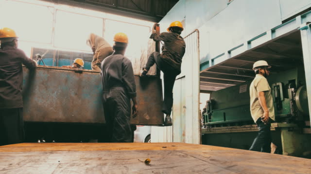 workers preparing to load steel plates on the truck at a factory - india stock videos & royalty-free footage