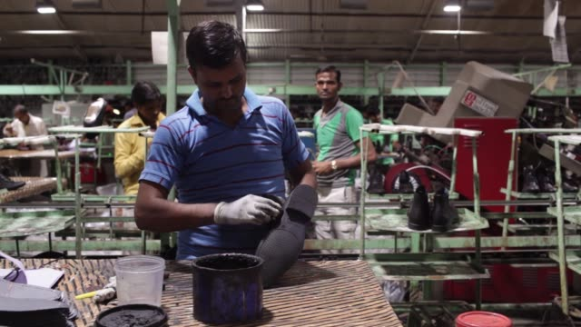workers push a rack of shoes past an assembly line at a virola shoes pvt manufacturing facility in agra uttar pradesh india on friday june 23 a... - shoes in a row stock videos & royalty-free footage