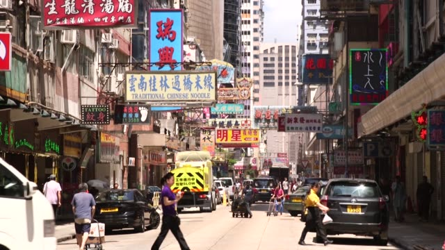 workers push carts as cars drive past in the mong kok district of hong kong china on monday sept 12 pedestrians cross a street in the mong kok... - mong kok stock videos and b-roll footage