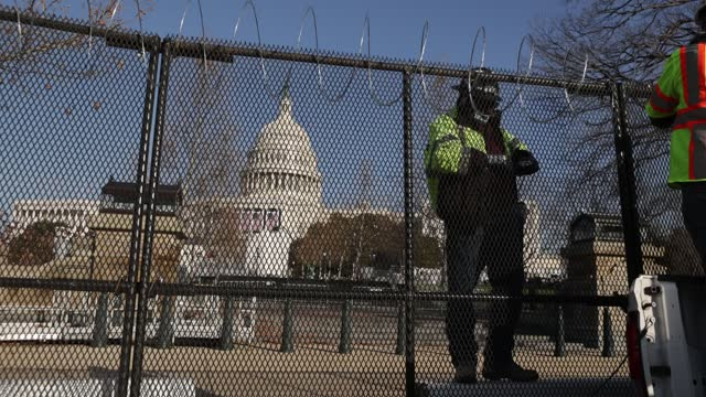 workers put concertina razor wire along the top of the 8-foot 'non-scalable' fence that surrounds the u.s. capitol the day after the house of... - 大統領就任式点の映像素材/bロール