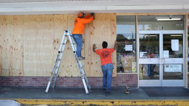 workers put plywood over the windows of a store as they prepare it in case hurricane dorian hits the area on august 31 2019 in delray beach florida... - preparation stock videos & royalty-free footage