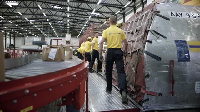 ベルトコンベアから、航空機輸送コンテナーにパッケージを入れて DS 労働者